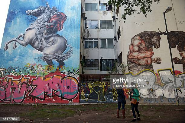 Tourists look at buildings decorated with murals in Buenos Aires on July 1 2015 The landscape of poor areas of the city has been enriched with murals...