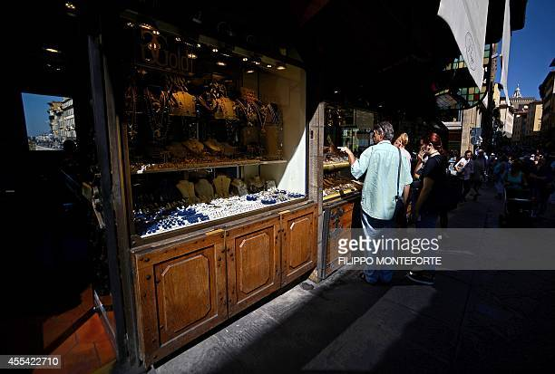 Tourists look at gold and jewelry shop windows on Florence's Ponte Vecchio a Medieval stone closedspandrel segmental arch bridge over the Arno River...