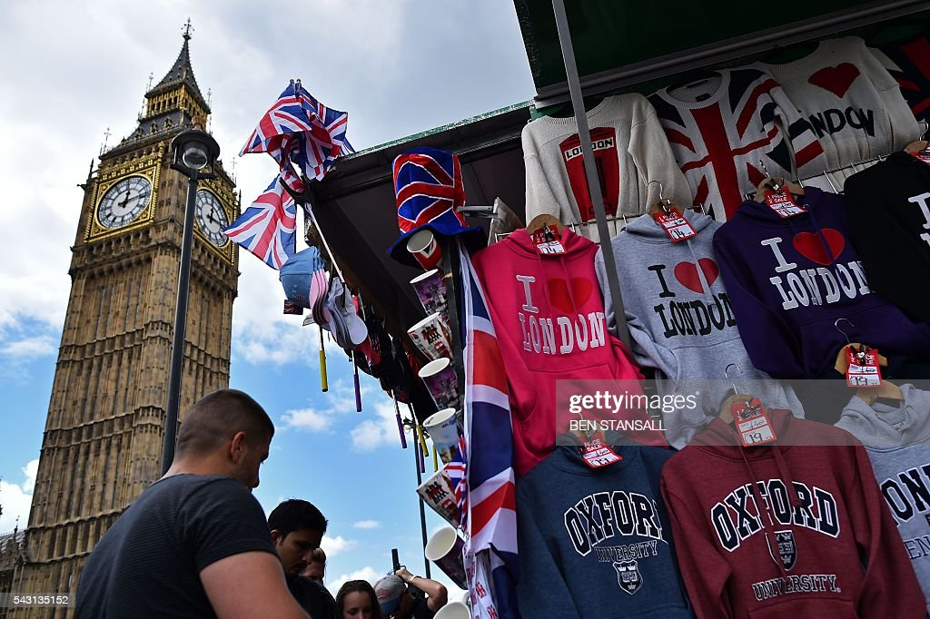 Tourists look at London-themed merchandise as Union flags fly above a street vendor's stall near the Big Ben clock face and the Elizabeth Tower at the Houses of Parliament in central London on June 26, 2016. Britain's opposition Labour party plunged into turmoil Sunday and the prospect of Scottish independence drew closer, ahead of a showdown with EU leaders over the country's seismic vote to leave the bloc. Two days after Prime Minister David Cameron resigned over his failure to keep Britain in the European Union, Labour leader Jeremy Corbyn faced a revolt by his lawmakers who called for him, too, to quit. STANSALL