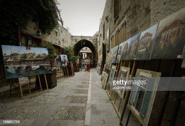 Tourists look at paintings displayed at an old market in the Lebanese ancient port city of Byblos on August 10 2010 AFP PHOTO/JOSEPH EID