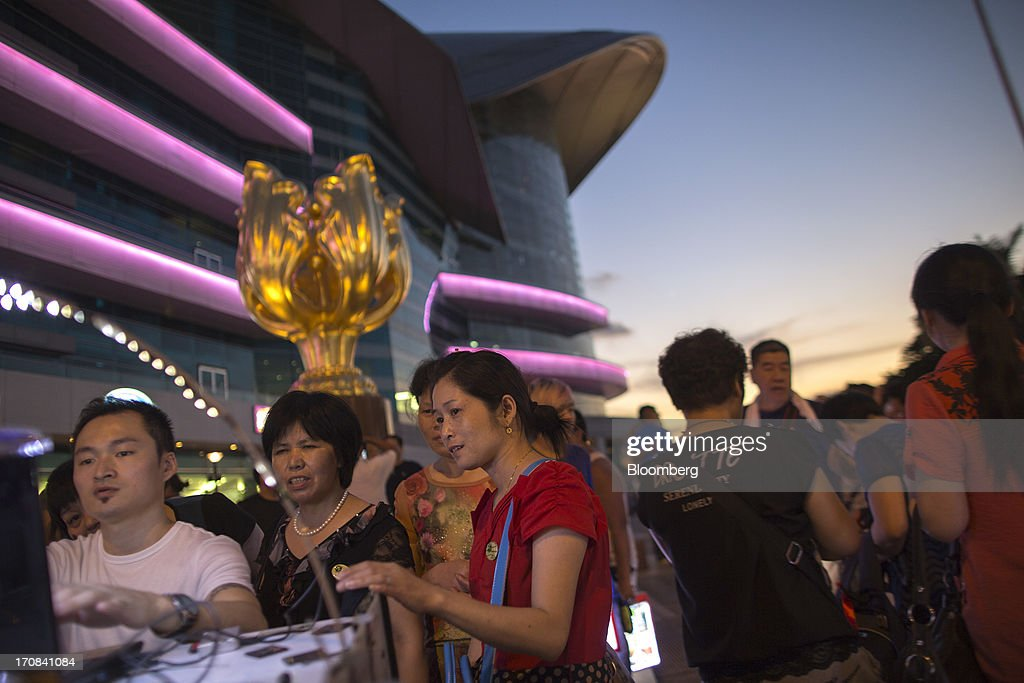 Tourists look at photographs on a photographer's laptop computer at Golden Bauhinia Square in Hong Kong, China, on Tuesday, June 18, 2013. A shortage of housing, low mortgage costs and a buying spree by mainland Chinese have led home prices to more than double since the beginning of 2009, shrugging off repeated attempts by the government to curb gains amid an outcry over affordability. Photographer: Jerome Favre/Bloomberg via Getty Images