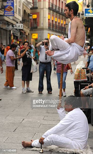 Tourists look at street artists performing a Fakir style act near the Puerta del Sol square in Madrid on June 26 2012 AFP PHOTO / DOMINIQUE FAGET