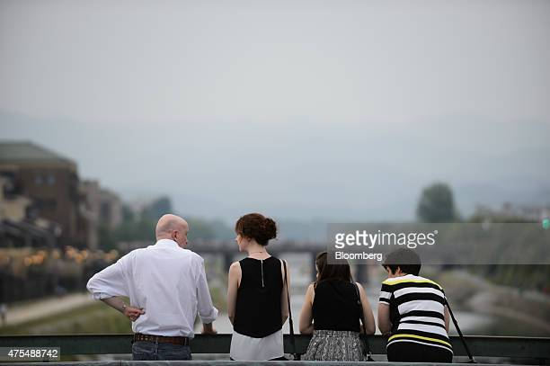 Tourists look at the Kamogawa river from a bridge in Kyoto Japan on Thursday May 28 2015 Spending by visitors to Japan jumped to the highest level in...