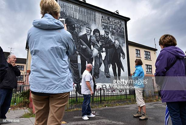 Tourists look at the mural on Free Derry Corner depicting an image of Bishop Daly as parishioners and well wishers pay their respects to the late...