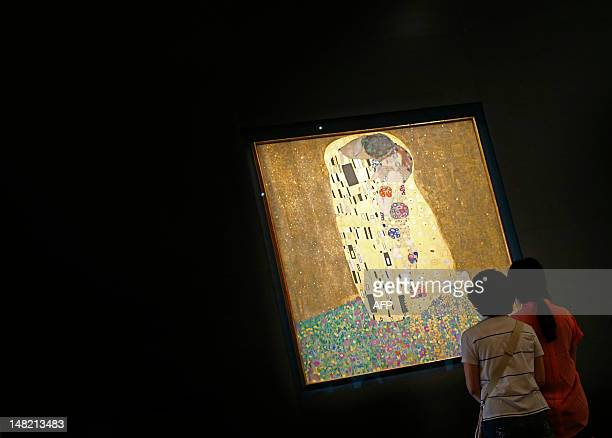 Tourists look at the painting 'The Kiss' by Austrian artist Gustav Klimt at the Belvedere Palace in Vienna on July 12 2012 Vienna's Belvedere Museum...