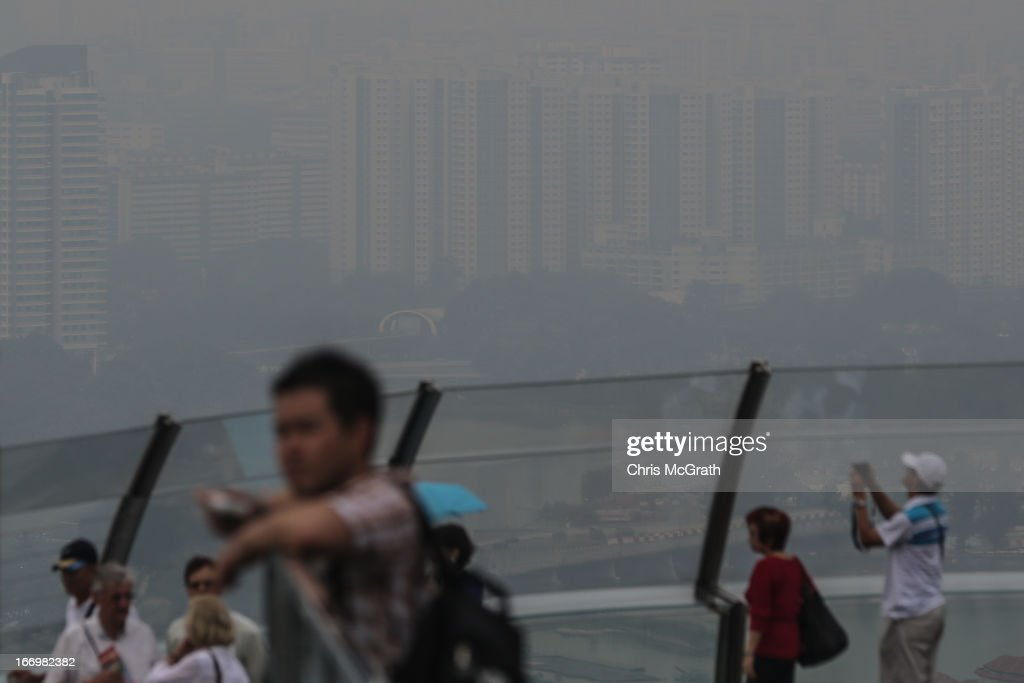 Tourists look at the Singapore skyline covered in smoke haze from Marina Bay Sands Sky Park on April 19, 2013 in Singapore. The haze was created by burning off in neighbouring Sumatra and caused the Pollutant Standards Index to rise, hovering between 28 and 43.