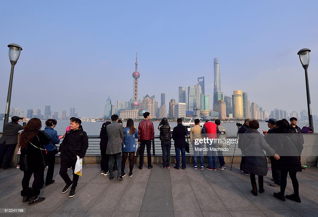 Tourists look at the view of the New Pudong Area the Financial Center of Shanghai with the Oriental Pearl TV Tower on February 25 2016 in Shanghai...