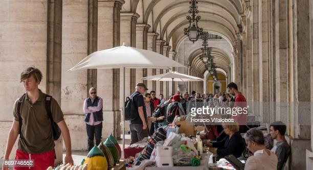 Tourists look for souvenirs at the artisans' fair under the arches of the Ministry of Justice in Praca do Comercio on October 21 2017 in Lisbon...