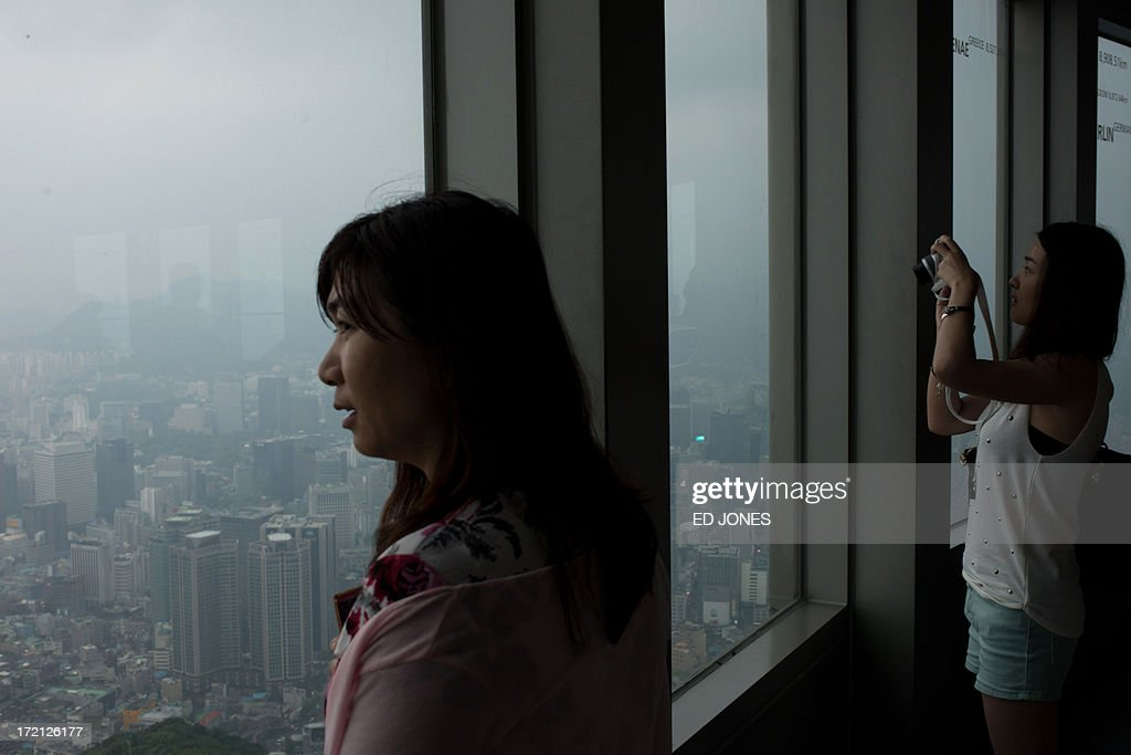 Tourists look from a window of the Namsan tower overlooking the Seoul city skyline during rainfall on July 2, 2013. July marks the wet season for Seoul during which the city of10 million people receives some 60 percent of its annual rainfall. AFP PHOTO / Ed Jones