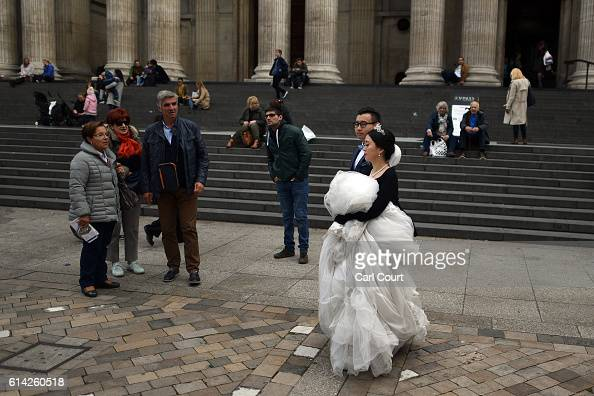 Tourists look on as Echo Li and her fiance Charles Qian walk in front of St Paul's Cathedral during a prewedding photography shoot on October 11 2016...