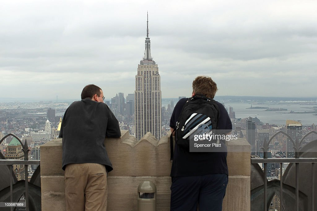 Tourists look out at the Empire State Building from the observation deck at Rockefeller Center on August 24, 2010 in New York City. A proposed tower on 34th Street would stand only 900 feet away from the iconic Empire State Building if it were to be completed. The new tower, which would be built at 15 Penn Plaza, has drawn criticism from the owners of the 102-storey Empire State Building, who say that at its current proposed height it would be just 34 feet shorter than the Empire State building and would severely alter the view of the Manhattan skyline. Standing at 1,250 feet at the 102nd floor, the Empire State building is currently the tallest building in New York.