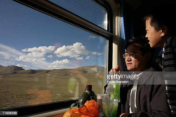 Tourists look out at the scenery onboard the QinghaiTibet railway on August 8 2006 heading towards Xinning Tibet Autonomous Region China Chinese...