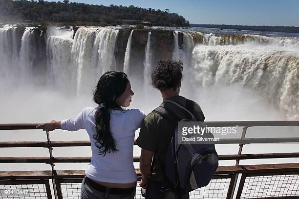 Tourists look over The Devil's Throat cataract towards the Floriano cataracts of the Brazilian side of the Iguacu Falls in the Iguazu National Park...