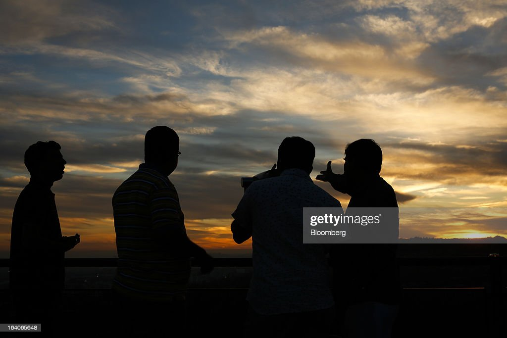 Tourists look towards the sunset from the Griffith Observatory in Los Angeles, California, U.S., on Thursday, March 14, 2013. California should start a state-run bank to finance economic development that's less polluting and more environmentally friendly, financed by auctions of greenhouse-gas carbon credits, Lieutenant Governor Gavin Newsom said. Photographer: Patrick T. Fallon/Bloomberg via Getty Images
