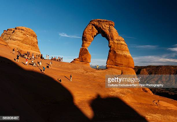 Tourists looking at Delicate Arch at sunset, Arches National Park, Utah, USA