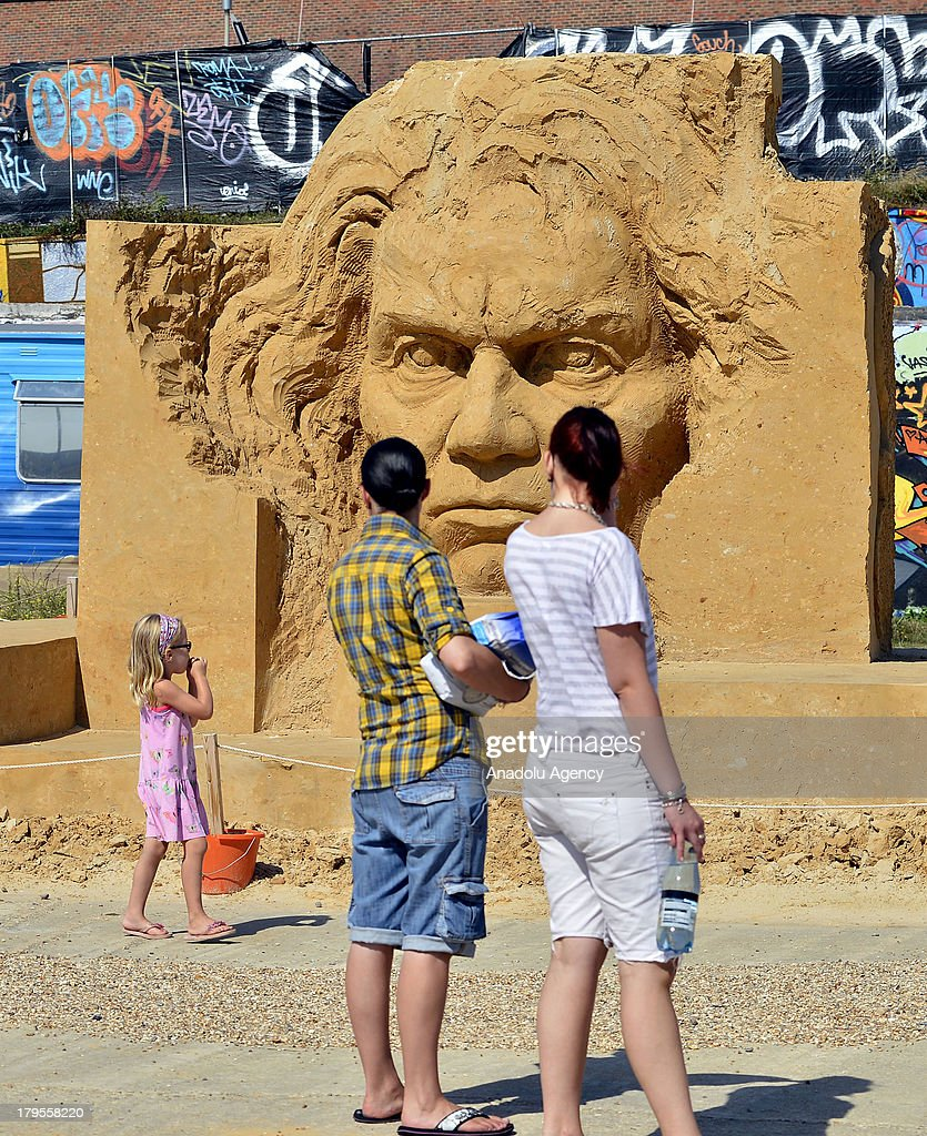 Tourists looking at the sand sculptures on the beach next to the mairna on 29 August 2013 in Brighton. Brighton, is one of the summer resorts today in UK which used to be a small fishing town and became more and more popular since a doctor called Richard Russell during the 1740's encouraged his patients to use a form of water therapy that involved the submersion or bathing in, and drinking of seawater. In addition to that, following the inauguration of the railroad, it got easier for Londoners to get there even for daytrips. Brighton Sand Sculpture Festival 2013 is held annually and the them for 2013 is Music.