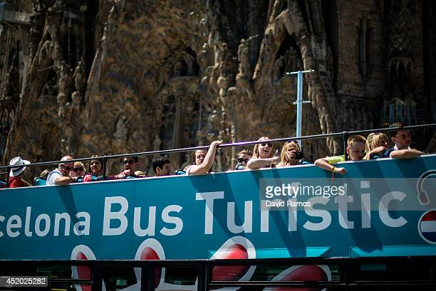 Tourists looks at La Sagrada Familia from a open top tour bus on July 11 2014 in Barcelona Spain As traders of 'La Boqueria' complain about tour...