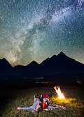Young couple tourists lying near the campfire under incredibly beautiful starry sky and Milky way at night. In the background silhouette of the mountains and luminous village in the valley. Low light