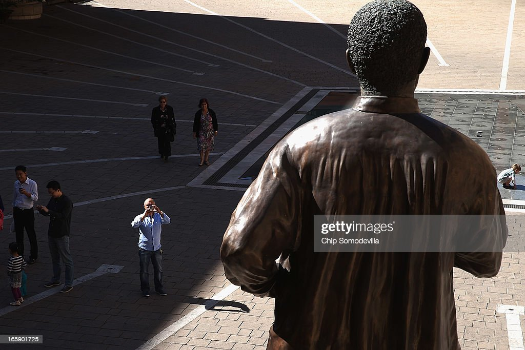 Tourists make photographs of the 20-foot-tall statue of former South African President Nelson Mandela in Mandela Square near the Sandton shopping district on April 7, 2013 in Johannesburg, South Africa. Mandela returned to his Johannesburg home yesterday after spending nine days in the hospital with pneumonia.