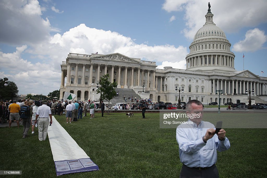 Tourists make photos near the Special Operations Speaks (SOS) Political Action Committee's 60-foot-long petition demanding a House Select Committee investigate the Benghazi terrorist attck outside the U.S. Capitol July 23, 2013 in Washington, DC. The scroll bears the names of more than 1,000 Special Service veterans who support a full investigation of the September 11, 2012, Benghazi attacks.