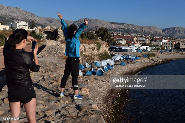 TOPSHOT Tourists make picture with tents on the beach next to the municipalityrun Souda refugee camp on the island on Chios on September 29 2016...