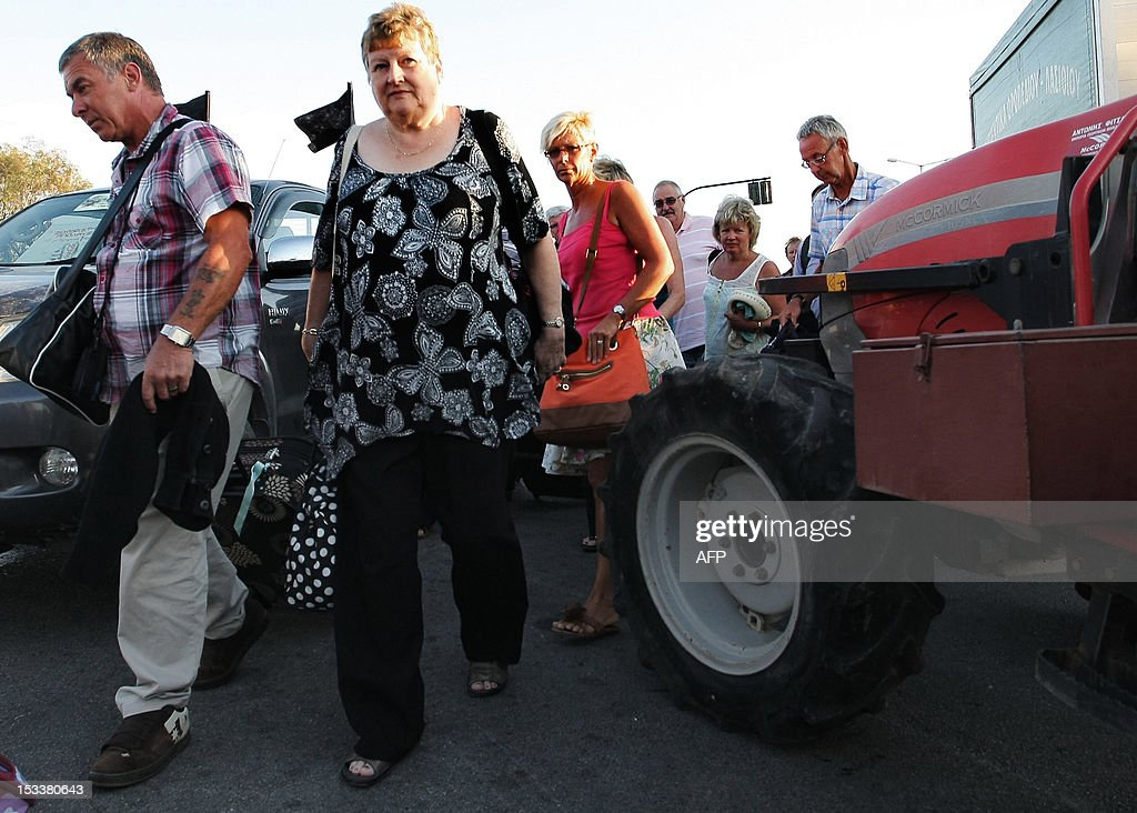 Tourists make their way through parked tractors as farmers block the international airport of Heraclion on October 4, 2012 on the Greek Island of Crete, to protest against new government austerity measuress. AFP PHOTO/ Costas Metaxakis