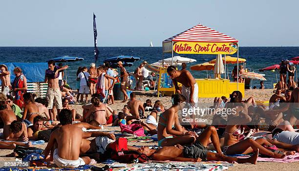 Tourists of various nationalities sunbathe by a water sport centre on Lloret beach on August 16 2008 in Lloret de Mar Spain Feeling the pinch from...