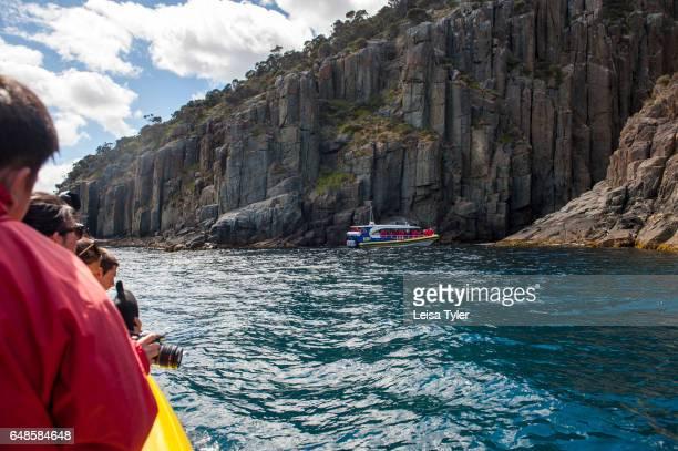PENINSULA TASMANIA AUSTRALIA Tourists on a Pennicott Wilderness Journey's cruise along the Tasman Peninsula coastline in Tasmania Home to the penal...