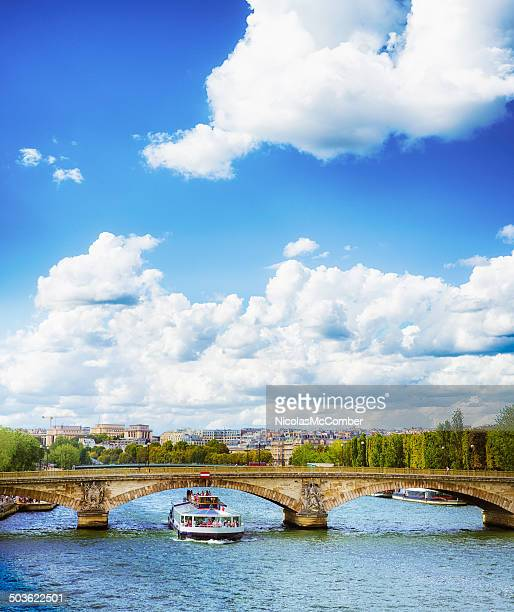 Tourists on a Seine cruise with cloudscape