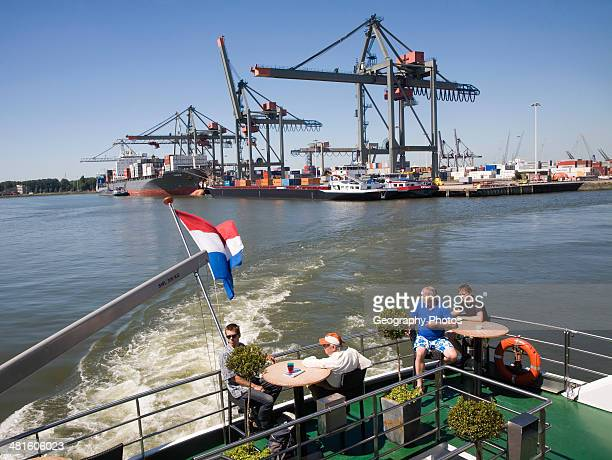 Tourists on a Spido tour boat in container port with quayside cranes and shipping activity Port of Rotterdam Netherlands