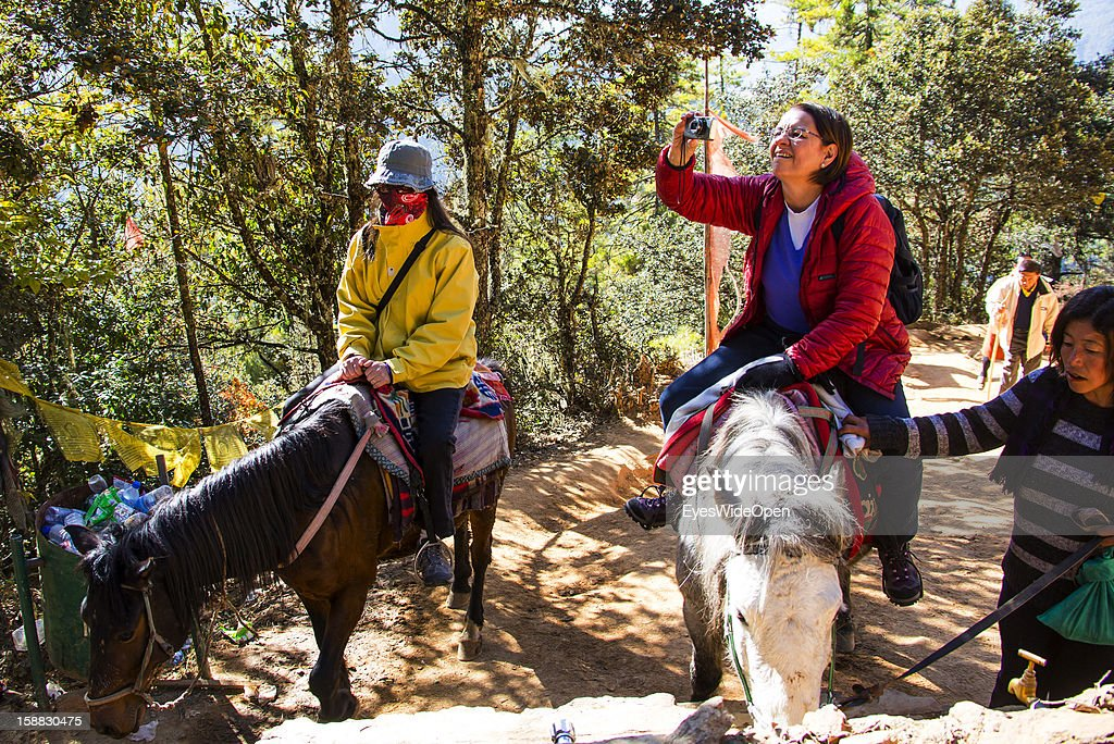 Tourists on horses on the way uphill to Paro Taktsang, also called Taktsang Palphug Monastery or Tiger `s Nest, a famous sacred site and temple complex reachable by a 3 hours footwalk for tourists and locals on November 18, 2012 in Paro near Thimphu, Bhutan. Its located in a valley near Paro surrounded by mountains and was built in 1692.