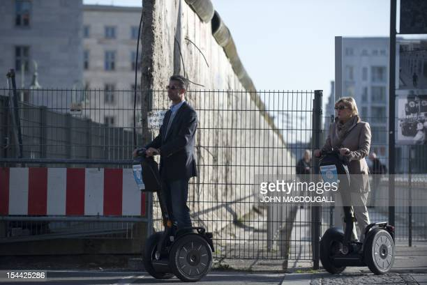 Tourists on Segways pass by a segment of the Berlin wall near the city's Potsdamer Platz on October 19 2012 Segway tours are growing in popularity in...