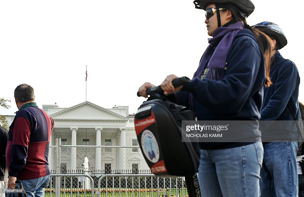 Tourists on Segways ride past construction for US President Barack Obama's second inauguration is under way in front of the White House in Washington on November 10, 2012. Obama won Florida's 29 electoral votes in the presidential election on November 10, further fattening his substantial margin of victory in what had been predicted to be a close race. The state was the last to report its tally from the election November 6, in which Obama beat Republican Mitt Romney. With Florida's votes in the electoral college, the president's total goes up to 332, against 206 for Romney. AFP PHOTO/Nicholas KAMM
