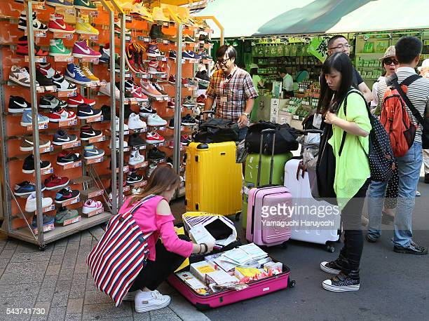 Tourists pack a purchase in to a suitcase in front of a shoe store at Ameyoko market in Tokyo Japan Sep 2013 Ameyoko is a bustling outdoor...