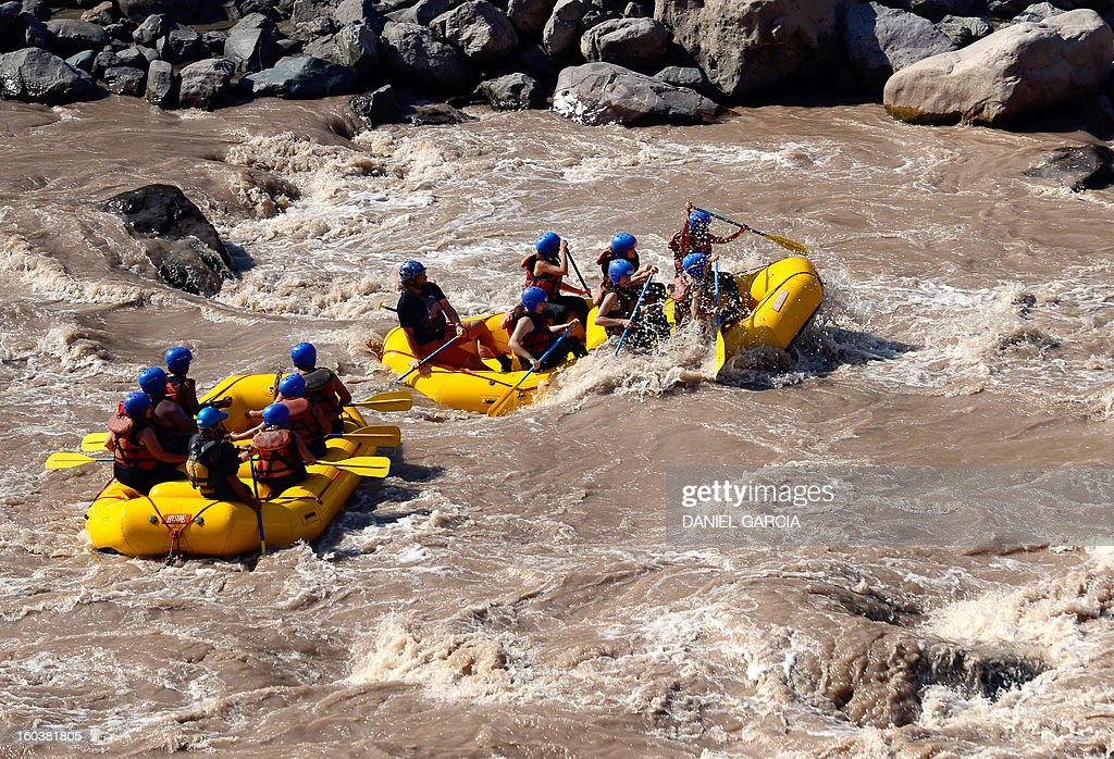 Tourists paddle through the rapids in the muddy waters of the Mendoza river near Potrerillos, Argentina on January 29, 2013.