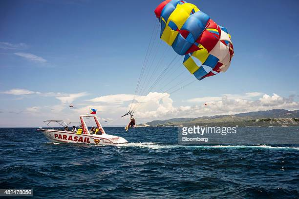 Tourists parasail off the shore of Boracay the Philippines on Tuesday July 28 2015 The Philippines an archipelago of more than 7000 tropical islands...