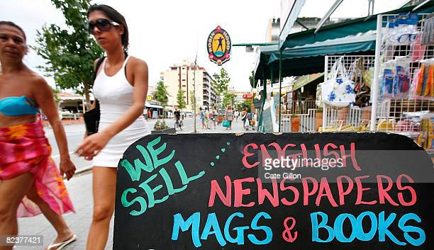 Tourists pass a sign advertising English merchandise at the 'British Food Imports' store on August 16 2008 in Lloret de Mar Spain With less British...