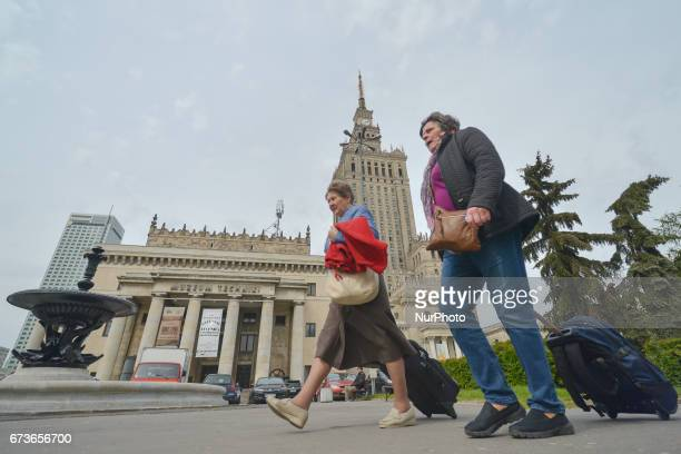 Tourists pass in front of the Palace of Culture and Science the tallest building in Poland On Tuesday April 26 in Warsaw Poland