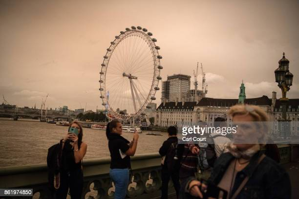 Tourists pass near the London Eye during a reddish sky caused by remnants of Hurricane Ophelia dragging in dust from the Sahara Desert on October 16...