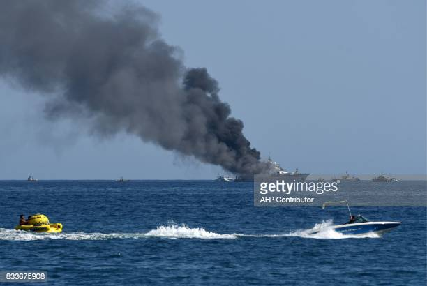 Tourists pass on speed boats as smoke rises from the boat 'If Only' a 39meterlong yacht that is on fire off SaintLaurentduVar near Nice southern...