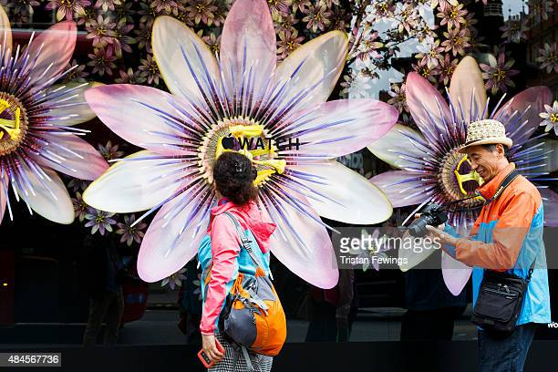 Tourists pass shop windows in which the Apple watch is displayed at Selfridges on August 20 2015 in London United Kingdom
