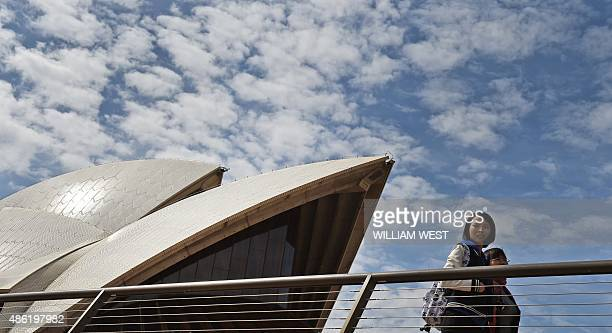 Tourists pass the Sydney Opera House on September 2 as data showed a boom in cashedup visitors from China and India has helped Australia to its...