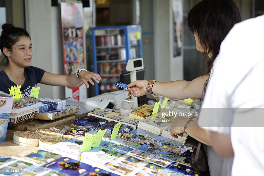 Tourists pay with a credi card after buying souvenirs at the Mont-Saint-Michel on August 11, 2012 in Le Mont-Saint-Michel, northwestern France. AFP PHOTO / CHARLY TRIBALLEAU