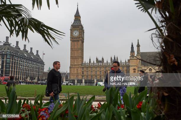 Tourists pedestrians and traffic move through the reopened Parliament Square in front of the Houses of Parliament in central London on March 24 2017...