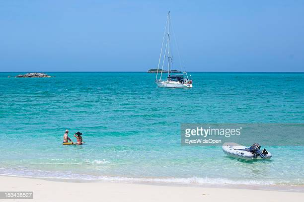 Tourists people a couple at the white sandy beach of Fernandez Bay are playing in the turquoise blue water of the caribbean sea with an anquered...