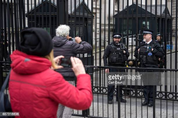 Tourists photograph armed police officers guarding Downing Street on March 24 2017 in London England A fourth person has died after Khalid Masood...