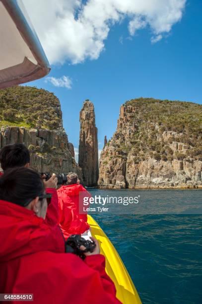 PENINSULA TASMANIA AUSTRALIA Tourists photograph the dramatic dolerite columns known as The Totem Pole and Candlestick on the Tasman Peninsula in...
