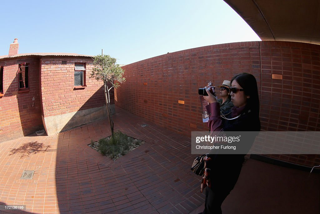 Tourists photograph the 'Mandela House' museum at 8115 in Vilakazi Street in the Orlando West section of Soweto Township on July 2, 2013 in Soweto, Johannesburg, South Africa. 8115 is the location of the first house owned by former South African President Nelson Mandela where he lived for 44 years from 1946 to 1990. The 'Mandela House', now a museum is managed by the Soweto Heritage Trust which has seen an increase in vistors both local and international since Mandela was hospitalized with a lung infection on June 8, 2013 and still remains in a critcal condition.