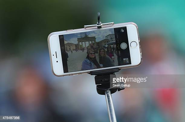 Tourists photograph themselves with a smartphone attached to a selfie stick at the Brandenburg Gate on May 19 2015 in Berlin Germany Selfie sticks...