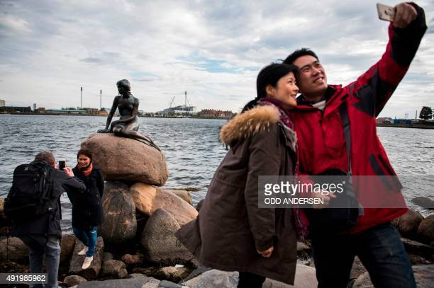 Tourists photograph themselves with the bronze statue 'The Little Mermaid' at the harbour in Copenhagen on October 9 2015 Based on the fairy tale of...
